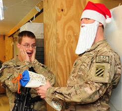 soldier in santa hat handing package to another soldier